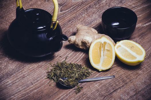 green tea with lemon and ginger with tea cup and teapot