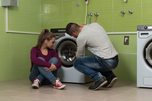 Young Couples Loading The Washing Machine In Room