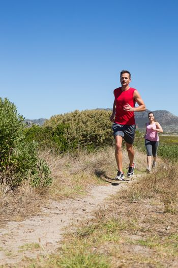 Active couple jogging on country terrain