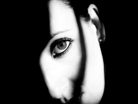 Eye looking to infinity shadows around. Horizontal rectangular artistic black and white digital photo.