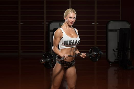 Young Woman Athlete Doing Heavy Weight Exercise For Biceps
