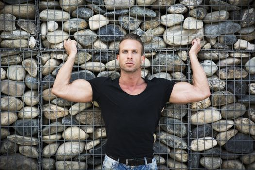 Muscular sexy man in front of stone wall,