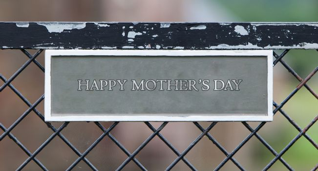 Sign hanging on an old metallic gate - Happy mothers day