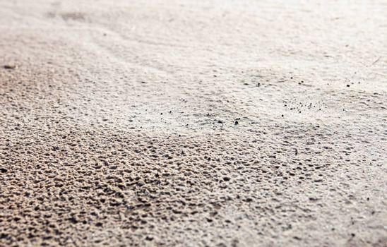 Sand surface after the rain with the visible traces of the raindrops