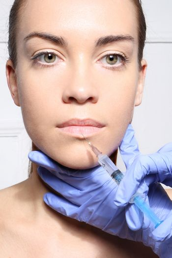 The face of a beautiful woman during the procedure of modeling the mouth, injecting