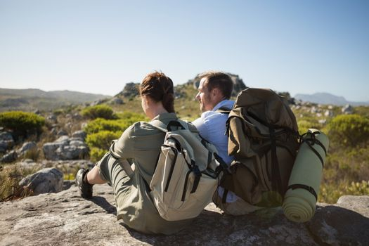 Hiking couple sitting on mountain terrain