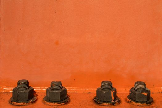 Orange painted background with four big bolts