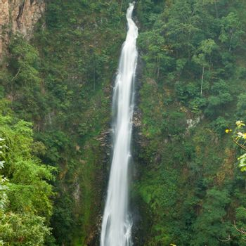 Waterfalls flowing down the cliff. High waterfall that flows down from the mountains into the cliffs.