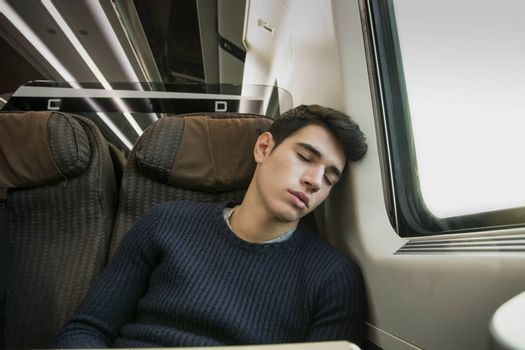 Young man sleeping while traveling on a train sitting in a passenger coach with his head resting on his hand and eyes closed