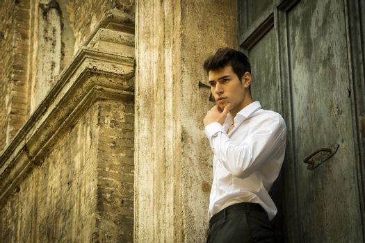 Elegant young man leaning against old wall and door, shot from below