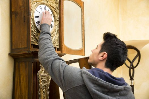 Young man checking the pendulum and winding the mechanism on a vintage long case clock standing with his back to the camera as he works