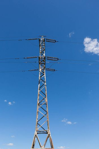 High voltage electric main against the dark blue sky