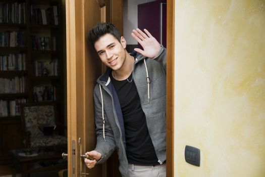 Smiling young man getting out of door waving at the camera with a friendly cheerful smile as he peers around the edge of a wooden door