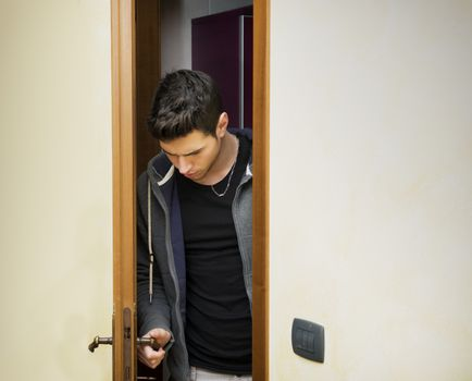 Handsome young man opening door to enter into a room, looking down at handle