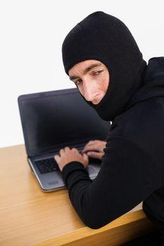 Burglar hacking a laptop and looking behind him