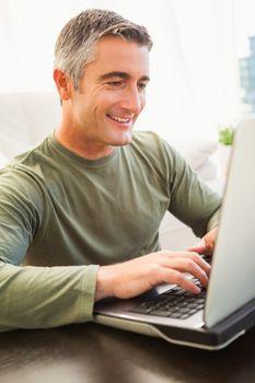 Smiling man with grey hair using laptop