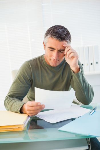 Smiling man with grey hair reading paper