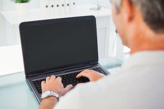 Man with grey hair typing on laptop