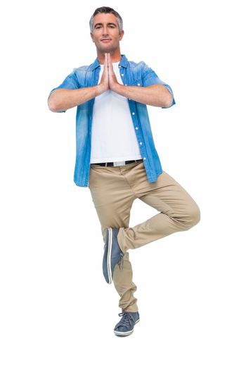 Man with grey hair in tree pose