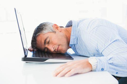 Man with grey hair sleeping on his laptop