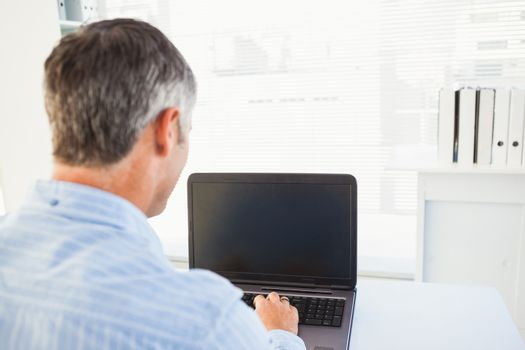 Man with grey hair using his laptop