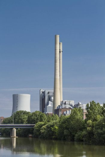 german coal-fired power station at the river Neckar with blue sky and bridge.