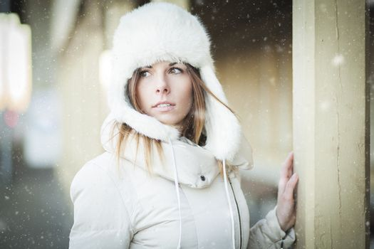 Young woman in fur hat and down jacket under falling snow