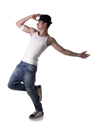 Hip young man in a tank top and hat doing a dance routine posing on one leg, isolated on white background