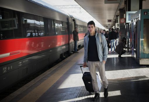Handsome young male traveler in train station with trolley suitcase, looking at camera