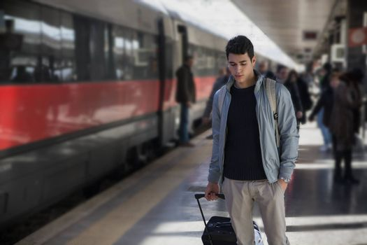 Handsome young male traveler in train station with trolley suitcase, looking down