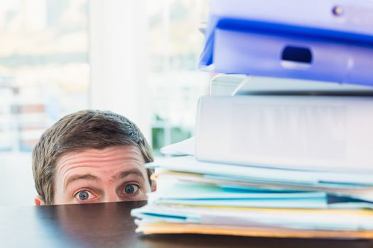 Scared businessman peeking over desk