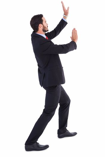 Businessman standing and pushing up
