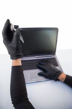 Burglar hacking laptop and mobile phone