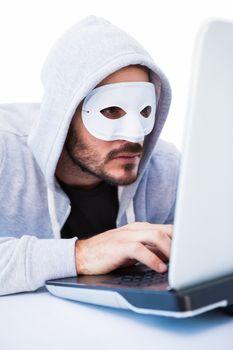 Man wearing mask while hacking into laptop
