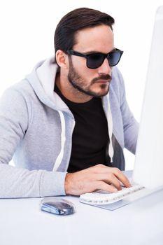 Man wearing sunglasses hacking into laptop