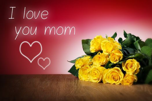 Bunch of yellow roses on a table and with red background, message I love you mum