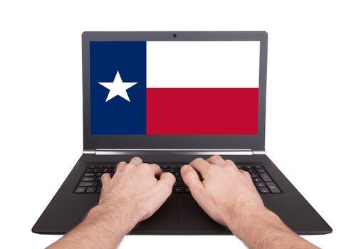 Hands working on laptop, Texas