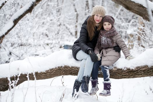 Portrait of a nine year girl with her mother in winter park