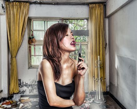 Chinese woman in abandoned aprtment about to lick a knife