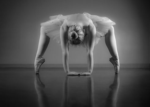 Graceful ballerina warming up in black and white