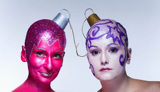 Two women with fantastic makeup posing as Christmas ornaments