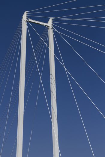 upper part of a suspension bridge with ropes and support before blue sky