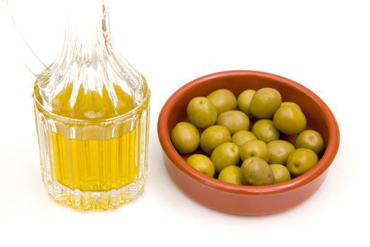 Rustic bowl of olives and olive oil on white background