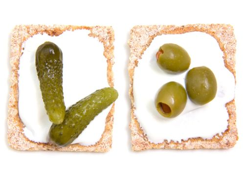 Canapes with gherkins and olives on a white background seen from above