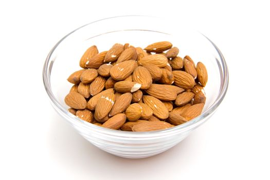 Almonds in glass bowl on white background