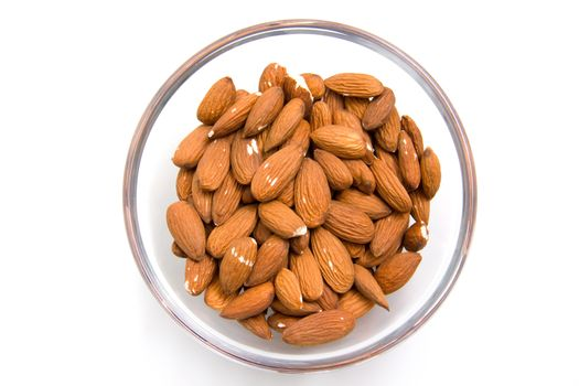 Almonds in glass bowl on white background from above