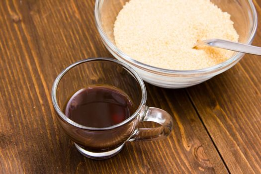 Coffee and bowl with brown sugar on wooden table from above