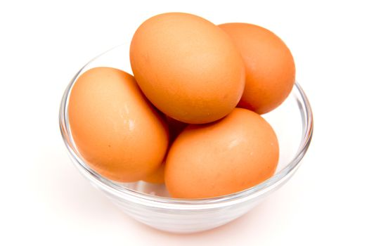 Eggs in glass bowl on white background