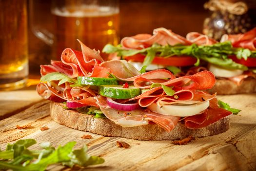 Two sandwiches with bacon and fresh vegetables on vintage wooden