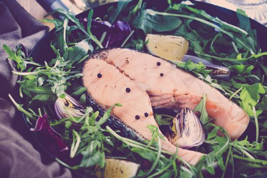 Salmon steak with fresh vegetables in a pan on a wooden table wi